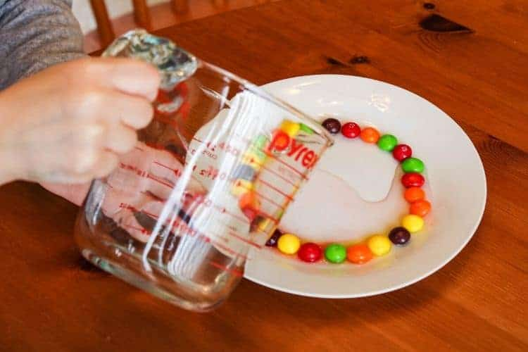 Girl pouring water on plate with Skittles