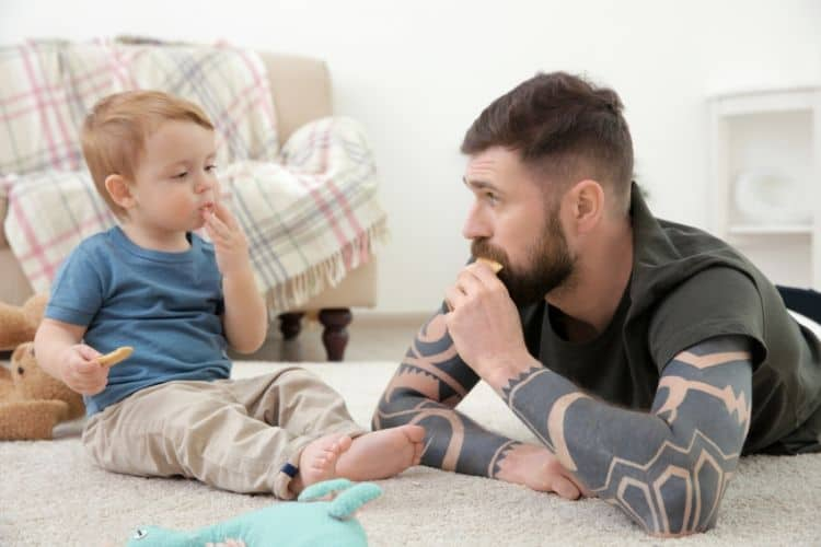 Dad and toddler looking at each other sitting on floor eating food