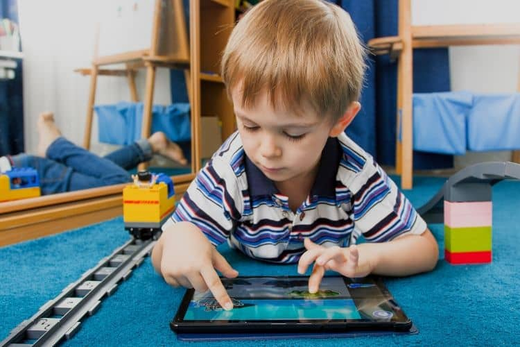 Boy laying on stomach on floor playing on a tablet