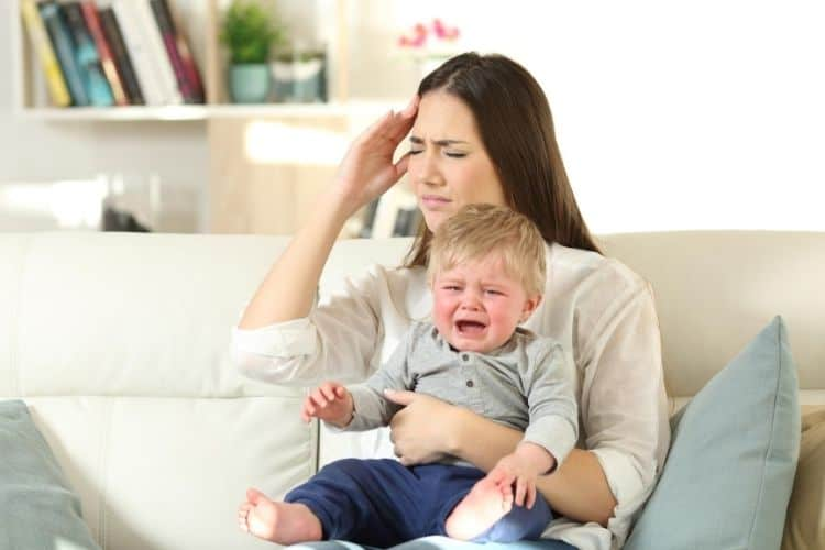 Exhausted mom holding a crying toddler while sitting on the couch
