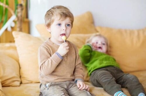 Toddler holding a sucker sitting on a couch with a sibling in the back also on couch