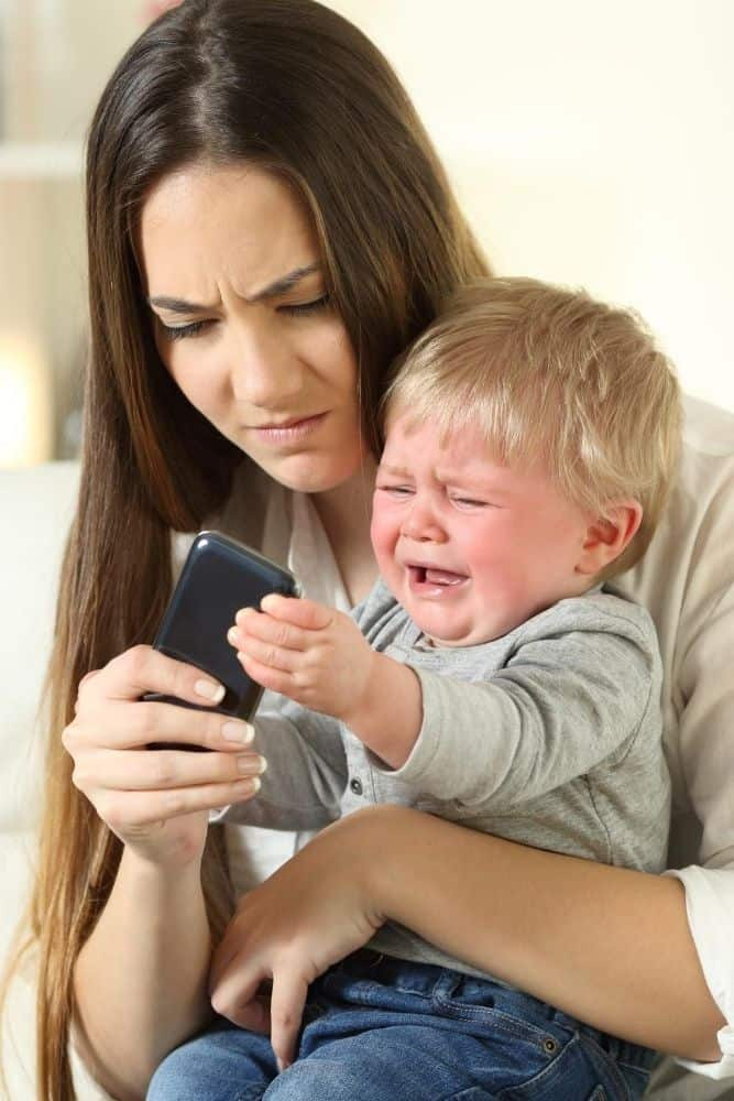 Mom playing with a smartphone while toddler is in her lap crying
