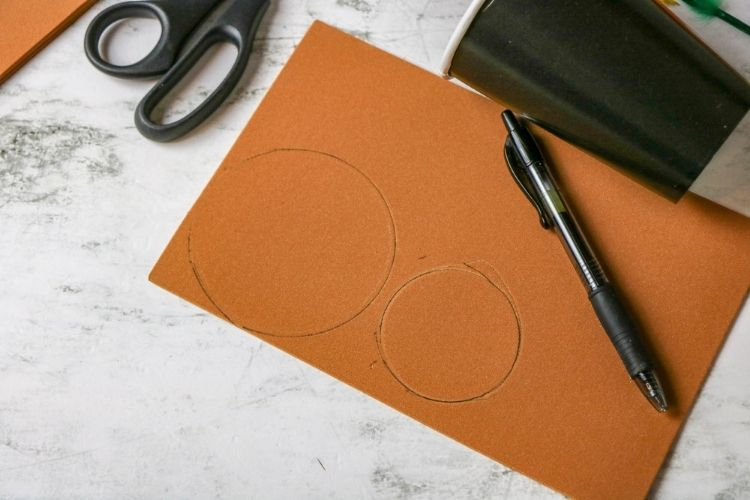 Two different sized circles traced onto a brown piece of foam craft paper