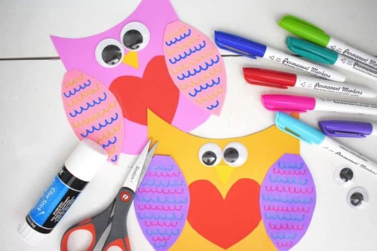 Valentine Owl Crafts with markers, a glue stick, and scissors next to them