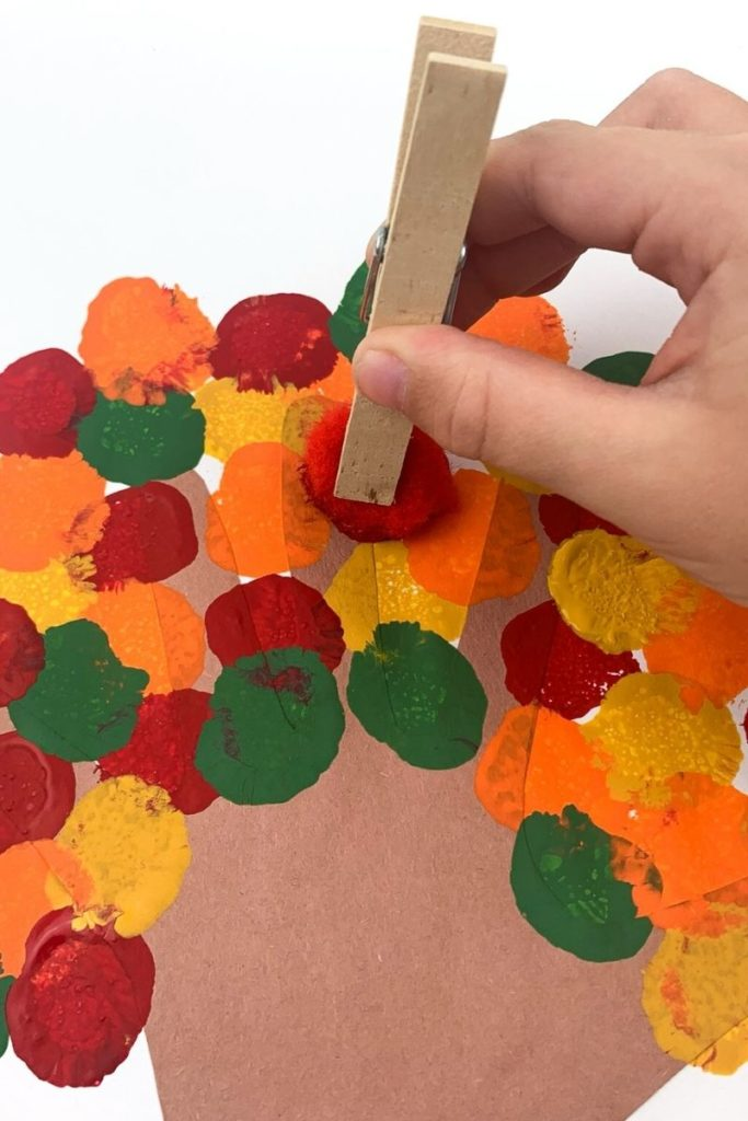 Dabbing paint leaves onto the fall craft