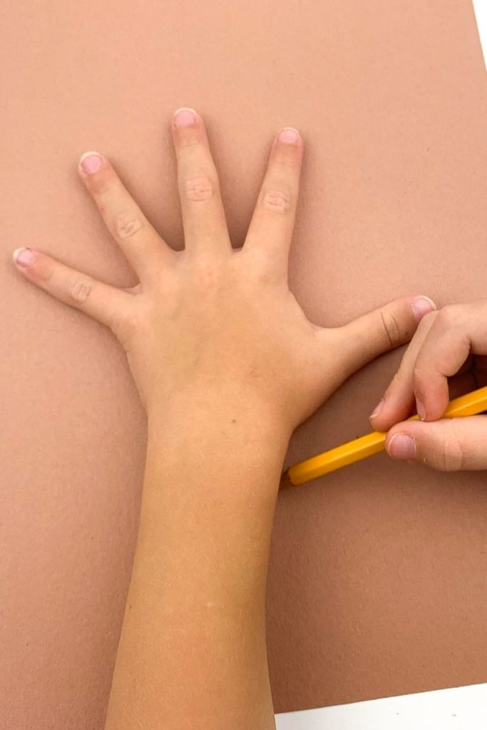 Tracing a hand and forearm on brown construction paper with a pencil