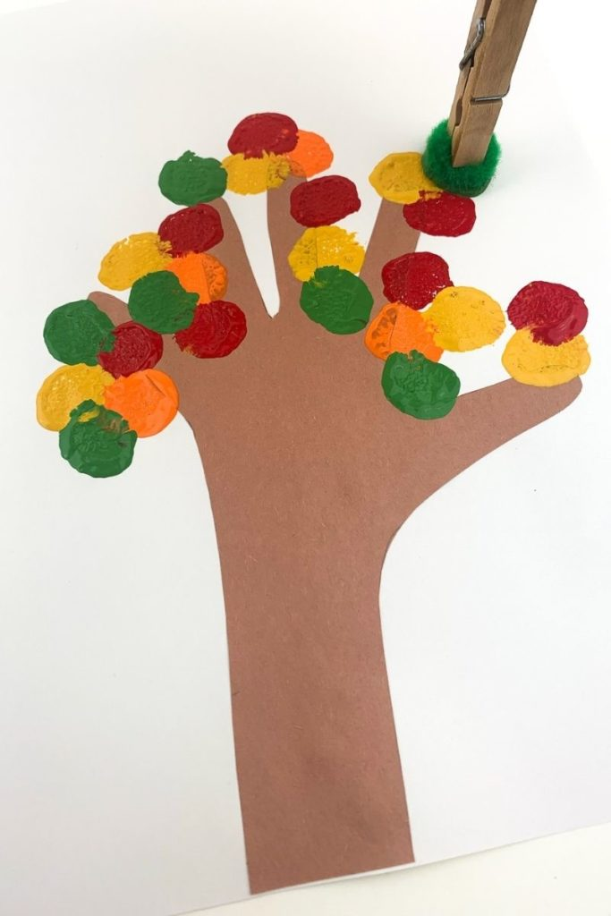 Stamping colors onto the tree to make a fall tree changing colors